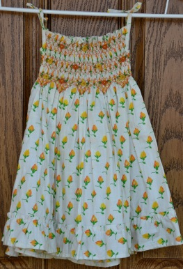 Orange and yellow floral on cream background. Smocked all the way around bodice (ie. same front and back). Age 1. Tie-up shoulders. 48cm long; 18cm wide.