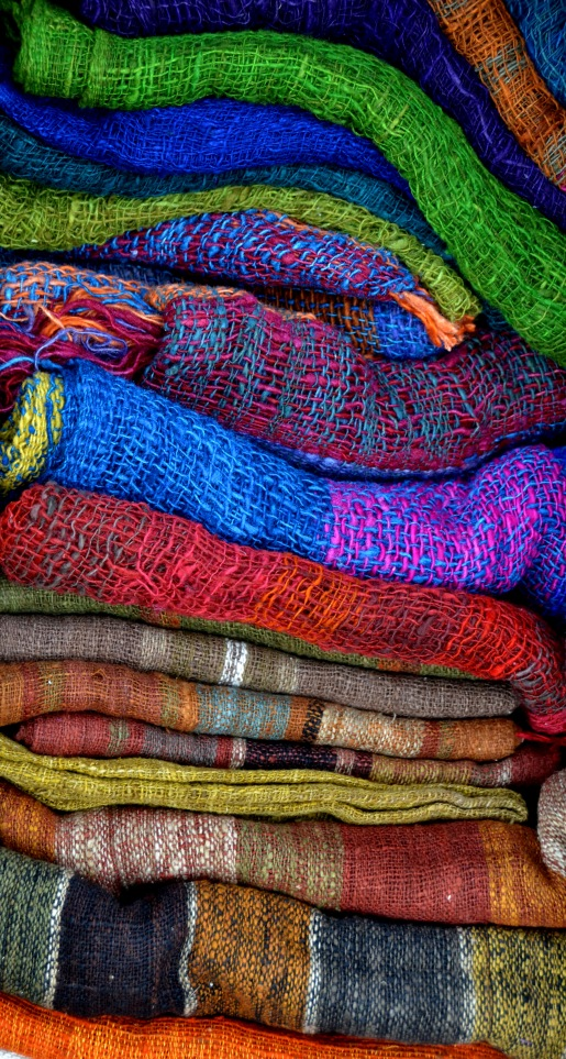 Assorted vibrant solid-coloured silk scarves. Hand woven.